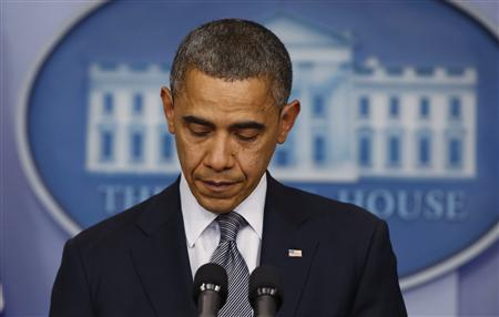 U.S. President Barack Obama pauses as he speaks about the shooting at Sandy Hook Elementary School in Newtown, Connecticut, during a press briefing at the White House in Washington December 14, 2012. REUTERS/Larry Downing