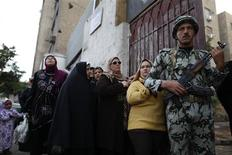 A soldier stands guard as women queue outside a polling center to vote in referendum on Egypt's new constitution in Cairo December 15, 2012. Polling stations opened on Saturday in a referendum on a new constitution shaped by Islamist allies of Egypt's President Mohamed Mursi and which his liberal rivals say deepens divisions in the nation. REUTERS/Khaled Abdullah