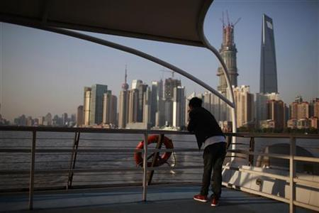 A man stands on a boat on the Huangpu River near the Pudong Lujiazui financial area in Shanghai November 12, 2012. REUTERS/Aly Song
