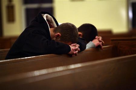 Two men pray at Saint Rose of Lima Roman Catholic Church near Sandy Hook Elementary School, where a gunman opened fire on school children and staff in Newtown, Connecticut December 14, 2012. REUTERS/Joshua Lott