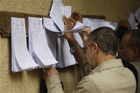 People look for their names at a polling station before casting their votes in a referendum on Egypt's new constitution in Cairo December 15, 2012. Egyptians queued to vote on Saturday on a constitution promoted by its Islamist backers as the way out of a prolonged political crisis and rejected by opponents as a recipe for further divisions in the Arab world's biggest nation. REUTERS/Khaled Abdullah (EGYPT - Tags: POLITICS ELECTIONS)