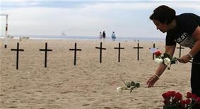 A woman puts a flower near crosses planted by NGO Rio de Paz (Rio Peace), in memory of the victims of the Sandy Hook Elementary school shooting in the U.S., on Copacabana beach in Rio de Janeiro December 15, 2012. A heavily armed gunman opened fire on school children and staff at Sandy Hook Elementary school on Friday, killing at least 26 people, including 20 children, in the latest in a series of shooting rampages that have tormented the United States this year. REUTERS/Sergio Moraes (BRAZIL - Tags: EDUCATION CRIME LAW)