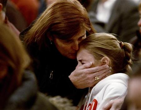 A woman comforts a young girl, during a vigil service at the St. Rose of Lima Roman Catholic Church, for victims of the Sandy Hook Elementary School shooting in Newtown, Connecticut, December 14, 2012. REUTERS/Andrew Gombert/Pool