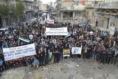 Manifestantes protestam contra ditador sírio Bashar al-Assad próximos a prédios danificados na cidade de Kafranbel. 14/12/2012. REUTERS/Raed Al-Fares/Shaam News Network/Handout