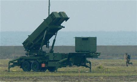A member of the Japan Self-Defence Forces runs toward a Patriot Advanced Capability-3 (PAC-3) missiles unit in Ishigaki on Japan's southern island of Ishigaki Island, Okinawa prefecture, in this photo taken by Kyodo December 12, 2012. REUTERS/Kyodo