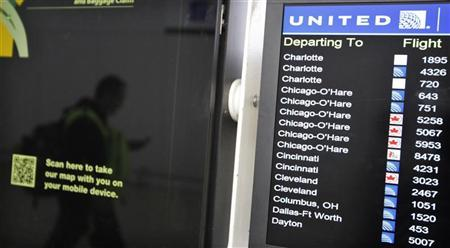 A customer is reflected in a screen showing the schedule times of United Continental Holdings Inc flights at Newark International airport in New Jersey , November 15, 2012. REUTERS/Eduardo Munoz
