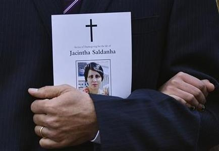 Jacintha Saldanha's widower Ben Barboza holds an order of service and the hand of his daughter Lisha (R) outside of Westminster Cathedral before a memorial service in London December 15, 2012. REUTERS/Toby Melville