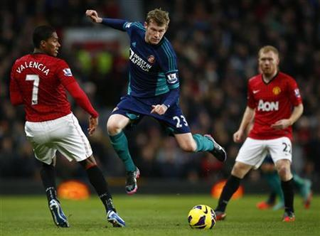 Manchester United's Antonio Valencia (L) challenges Sunderland's James McClean during their English Premier League soccer match at Old Trafford in Manchester, northern England, December 15, 2012. REUTERS/Darren Staples