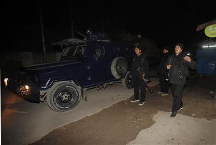 Policemen gather near the site of a rocket attack at Peshawar's airport December 15, 2012. Four people were killed when militants attacked the airport in the northwestern city of Peshawar on Saturday and traded gunfire with soldiers for more than 30 minutes before being repulsed, military and health officials said. REUTERS/Fayaz Aziz