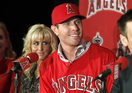 Los Angels Angels newly acquired outfielder Josh Hamilton talks with reporters as his wife, Katie, looks on during a news conference at the ESPNZone in Downtown Disneyland in Anaheim, California December 15, 2012. The Angels signed the free-agent and five-time All-Star to a five-year, $125 million deal. REUTERS/Alex Gallardo