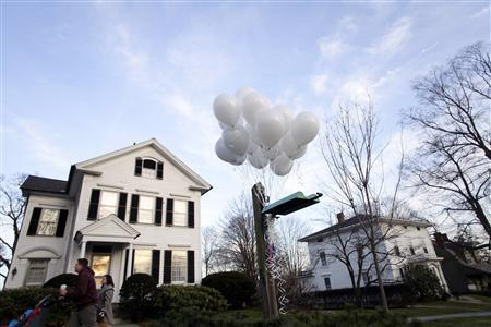 A couple and their child walk past twenty balloons tied in the front yard of a home, for the twenty children that were killed at Sandy Hook Elementary School, in Newtown, Connecticut December 15, 2012. REUTERS/Joshua Lott