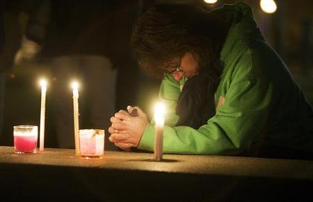 Paula Sullo prays at the New Haven Green during a candlelight vigil to support victims of the Sandy Hook Elementary School shooting in New Haven, Connecticut, December 15, 2012. REUTERS/Michelle McLoughlin