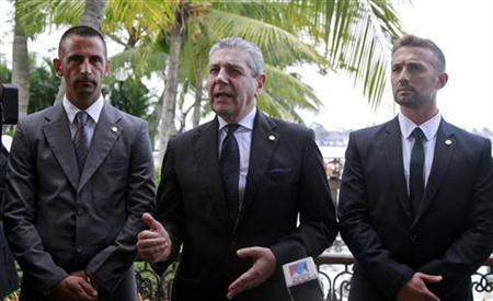 Italian Defense Minister Giampaolo di Paola (C) speaks at a news conference as Italian sailors Salvatore Girone (R) and Massimiliano Latorre stand beside him at a hotel lawn in Kochi December 16, 2012. REUTERS/Sivaram V