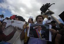 El presidente de Venezuela, Hugo Chávez, continúa mejorando y ya se encuentra en plenitud de sus condiciones intelectuales, dijo el sábado el Gobierno, después de una arriesgada operación quirúrgica a la que se sometió en Cuba para tratar un cáncer contra el que lucha desde hace un año y medio, y que amenaza con alejarlo del poder. En la imagen partidarios del Partido Libertad y Refundación (LIBRE) muestran imágenes de Chávez en un acto para rezar por la salud del mandatario venezolano en Tegucigalpa, el 15 de diciembre de 2012. REUTERS/Jorge Cabrera
