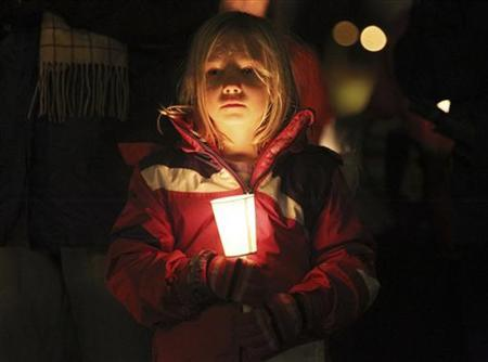 Seven-year-old Scout Elizabeth Noble of Seattle holds a candle while attending a vigil for victims of a Connecticut school shooting at Green Lake Park, Seattle December 15, 2012. Twelve girls, eight boys and six adult women were killed in the shooting on Friday at the Sandy Hook Elementary School in Newtown, Connecticut, the state's chief medical examiner said on Saturday. Dressed in ''cute kid stuff,'' all 20 children died when heavily armed 20-year-old gunman Adam Lanza forced his way into their school, Sandy Hook Elementary, and shot them and six women in an act of violence that has shattered their once-tranquil suburban town. REUTERS/Anthony Bolante (UNITED STATES - Tags: CRIME LAW EDUCATION)