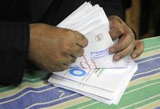 An electoral worker counts ballots after polls closed in Zagazig, about 62.5 km (38.8 miles) northeast of Cairo December 15, 2012. Egyptians queued in long lines on Saturday to vote on a constitution promoted by its Islamist backers as the way out of a political crisis and rejected by opponents as a recipe for further divisions in the Arab world's biggest nation. REUTERS/Stringer (EGYPT - Tags: POLITICS ELECTIONS)