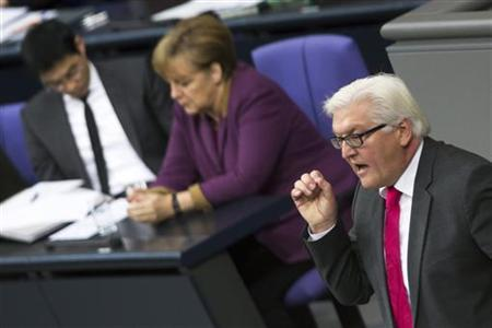 The leader of the parliamentary faction of the Social Democratic Party (SPD) Frank-Walter Steinmeier (R) speaks at the lower house of parliament, the Bundestag in Berlin, before the house votes on financial help for Greece, November 30, 2012. Germany's lower house of parliament will approve a fresh bailout for Greece on Friday in a vote seen as a test of Chancellor Angela Merkel's authority over her centre-right coalition less than a year before federal elections. Pictured in the background is German Chancellor Angela Merkel (2nd L) and Economy Minister Philipp Roesler (L). REUTERS/Thomas Peter (GERMANY - Tags: POLITICS BUSINESS)