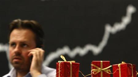 A share trader uses a mobile phone next to Christmas decorations in front of the German share price index DAX board at the German stock exchange in Frankfurt December 10, 2012. REUTERS/Lisi Niesner (GERMANY - Tags: BUSINESS)
