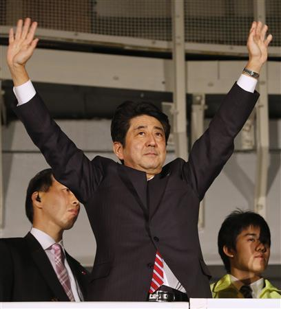 Japan's main opposition Liberal Democratic Party's (LDP) leader and former Prime Minister Shinzo Abe raises his hands atop a campaign van at Akihabara electronics store district in Tokyo December 15, 2012, on the last election campaign day ahead of Sunday's general election. REUTERS/Yuriko Nakao