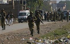 Pakistani army soldiers run towards a gun battle with Taliban militants near Peshawar's airport December 16, 2012. Militants holed up in a half-built house in the northwestern Pakistani city of Peshawar traded gunfire with police on Sunday after taking part in an attack on a nearby airport the previous night, officials said. REUTERS/Khuram Parvez