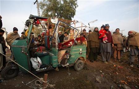 People gather around a rickshaw damaged during a rocket attack on Saturday night near a boundary wall of Peshawar's airport December 16, 2012. REUTERS/Fayaz Aziz