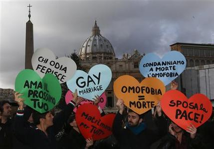 Members of a gay activist group hold signs in front of St. Peter's square in the Vatican December 16, 2012. REUTERS/Alessandro Bianchi