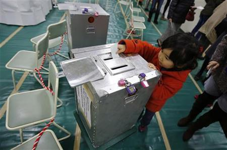 Haruka Tobe casts a ballot for her parents at a polling station located inside an elementary school in Tokyo December 16, 2012. Japan voted on Sunday in an election expected to return the conservative Liberal Democratic Party (LDP) to power after a three-year hiatus, giving ex-Prime Minister Shinzo Abe a chance to push his hawkish security agenda and radical economic recipe. REUTERS/Yuriko Nakao (JAPAN - Tags: POLITICS ELECTIONS)