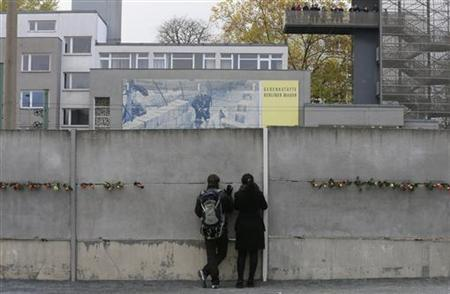 People look through a crack of at a concrete barrier that is part of the former Berlin Wall border fortification at the memorial site in Bernauer Strasse in Berlin November 9, 2012. REUTERS/Tobias Schwarz/Files