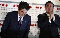 El conservador Partido Democrático Liberal (PDL) de Japón retornará al poder después de las elecciones del domingo, justo tres años después de sufrir una devastadora derrota en las urnas, lo que brinda al ex primer ministro Shinzo Abe la oportunidad de aplicar unas radicales medidas económicas. En la imagen, Abe (izquierda) hace una reverencia mientras el secretario general del partido aplaude en la sede de la formación en Tokio, el 16 de diciembre de 2012. REUTERS/Yuriko Nakao