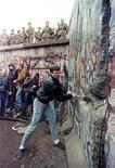 """La mayoría de los alemanes del este consideran a sus compatriotas occidentales unos """"arrogantes"""" que están interesados sobre todo en el dinero, según un nuevo estudio que subraya las diferencias entre ambos. En la imagen de archivo, un hombre golpea el Muro de Berlín el 11 de noviembre de 1989. REUTERS/David Brauchli/File Photo"""