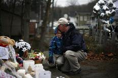 Los fieles abarrotaban el domingo los servicios religiosos en recuerdo de las víctimas del tiroteo en una escuela de primaria en la que murieron 20 niños y seis adultos, mientras el presidente de Estados Unidos Barack Obama tiene previsto asistir a una vigilia interreligiosa para ayudar a la devastada población a recuperarse. En la imagen, un hombre abraza a un niño en un memorial cerca de la escuela elemental Sandy Hook en Newtown, el 16 de diciembre de 2012. REUTERS/Eric Thayer