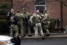 Equipe da polícia especial SWAT se prepara para entrar em igreja Saint Rose of Lima em Newtown, nos EUA. A igreja fica próxima à escola onde 20 crianças foram mortas na sexta-feira por um atirador.