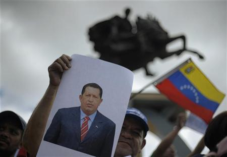 A supporter of the Liberty and Refoundation Party (LIBRE) holds up an image of Venezuelan President Hugo Chavez as he attends a rally to pray for Chavez's health in Tegucigalpa December 15, 2012. REUTERS Jorge Cabrera