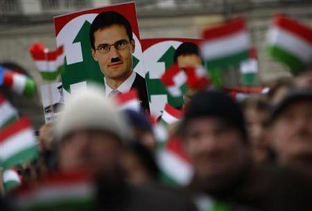 A defaced photo of Marton Gyongyosi, a leader of Hungary's far-right political party Jobbik, is seen on a placard during a demonstration against Nazism in front of the Parliament building in Budapest December 2, 2012. REUTERS/Bernadett Szabo