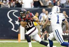 Houston Texans linebacker Bryan Braman scores a touchdown after recovering a blocked punt as Indianapolis Colts punter Pat McAfee tries to catch him during the first half of their NFL football game in Houston December 16, 2012. REUTERS/Donna Carson