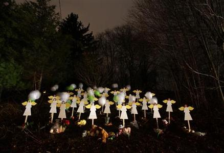 Twenty-seven wood painted angels are displayed outside of a home to honor the victims killed at Sandy Hook Elementary School in Newtown, Connecticut December 16, 2012. REUTERS/Joshua Lott