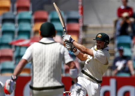 Australia's Ed Cowan (R) hits a boundary to bring up the century partnership with team mate David Warner (L) during the fourth day's play in their first cricket test match against Sri Lanka at Bellerive Oval in Hobart December 17, 2012. REUTERS/David Gray
