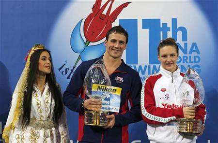 Ryan Lochte (C) of the U.S. and Katinka Hosszu (R) of Hungary pose with their trophies for best swimmers during the award ceremony at the FINA World Swimming Championships in Istanbul December 16, 2012. REUTERS/Murad Sezer