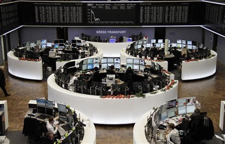 Traders are pictured at their desk in front of the DAX board at the Frankfurt stock exchange December 13, 2012. REUTERS/Remote/Pawel Kopczynski