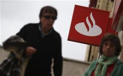La bolsa española iniciaba la primera sesión de la semana con pocos cambios y el interés inversor puesto sobre los bancos Santander y Banesto después de que el primero dijera que va a analizar la fusión por absorción del segundo. En la imagen, dos personas pasan junto a una sucursal de Santander en Madrid el 25 de octubre de 2012. REUTERS/Sergio Pérez