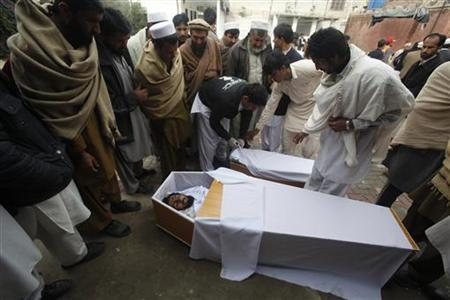 People try to identify their relatives who were killed during a bomb attack at Fauji Market in Peshawar December 17, 2012. REUTERS/Fayaz Aziz