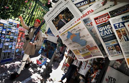 A presidential guard marches by a newspaper stand featuring news about Greece's election results in Athens in this June 18, 2012 file picture. REUTERS/Pascal Rossignol/Files