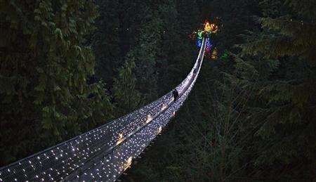Visitors walk across the Capilano Suspension Bridge decorated in Christmas lights in North Vancouver, British Columbia December 10, 2012. REUTERS/Andy Clark