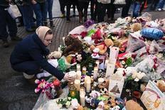 """La pequeña localidad de Newtown, en el estado de Connecticut, golpeada por un suceso que el presidente Barack Obama calificó de """"mal sin escrúpulos"""", celebra el lunes los primeros dos de los 20 funerales por los niños que murieron la semana pasada asesinados en sus aulas. En la imagen del 16 de diciembre, una chica coloca una vela en el memorial en Newtown en recuerdo a las víctimas. REUTERS/Lucas Jackson"""