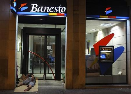 A man sleeps outside a Banesto bank branch in central Barcelona June 27, 2012. REUTERS/Andrea Comas