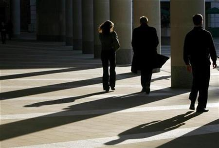 Workers walk outside the London Stock Exchange October 16, 2008. REUTERS/Andrew Winning