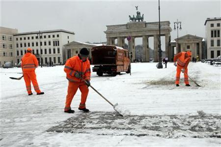 Municipal workers clear the snow from the pathway near the Branderburg gate in Berlin February 21, 2012. REUTERS/Ints Kalnins (GERMANY - Tags: ENVIRONMENT)