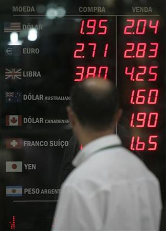 A man walks past a board showing the Real-U.S. dollar exchange rates in Rio de Janeiro, in this file photo taken May 16, 2007. REUTERS/Bruno Domingos