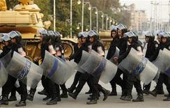 La oposición convocó protestas en todo Egipto contra la constitución apoyada por el presidente Mohamed Mursi, después de que el referéndum expusiera profundas divisiones que podrían minar sus intentos de alcanzar un consenso sobre duras medidas económicas. En la imagen del 16 de diciembre se puede ver a unos policías antidisturbios al desplegarse ante el palacio presidencial de El Cairo. REUTERS/Khaled Abdullah