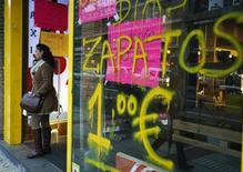 Las previsiones de invierno elaboradas por Ernst & Young (E&Y) para la economía española en 2013 son más negativas que las del Gobierno, al situar el crecimiento del PIB, la tasa de desempleo y el déficit en niveles que empeoran las proyecciones del Ejecutivo debido a la restricción del crédito y las incertidumbres. En la imagen del 14 de diciembre, una mujer sale de una tienda en Madrid. REUTERS/Sergio Pérez